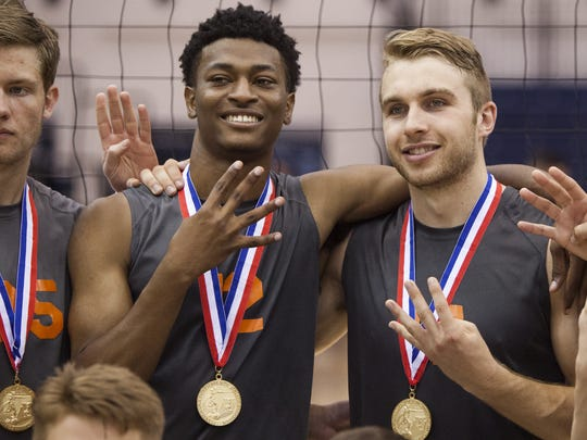 Devilbiss, right, and teammate Jeff Reynolds hold up the No. 4 following the PIAA championship match: as in four-straight state titles for the Bobcats' volleyball program.