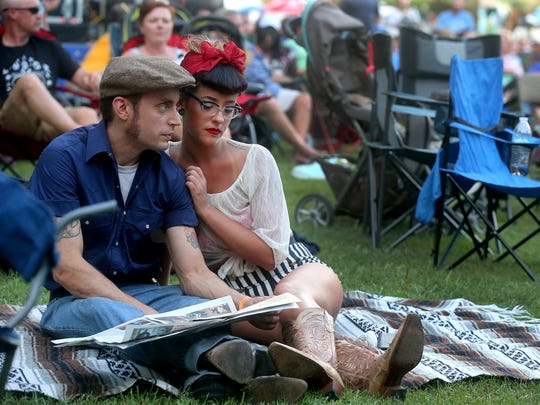 Jeremiah Cline, left, and Cheyann Tucker, right, cuddle up in the grass as they listen to the sounds of Flatt Lonesome, during the 39th Annual Uncle Dave Macon Days Festival, on Friday, July 08, 2016.