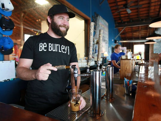 Burley Oak Brewery owner Bryan Brushmiller pours a beer at the brewery in downtown Berlin.