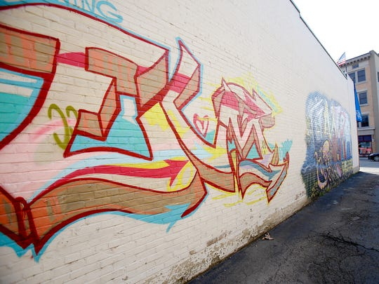 """Two murals decorate the side of Kingsbury's Cyclery in downtown Elmira. The murals — an octopus painted by Jesse Orme and the letters """"Elm"""" designed by Courtney Byfield — were commissioned and completed during the Elmira Street Painting Festival in July."""