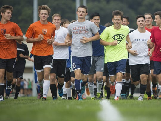 Players for the Central York High School boys' soccer team warm up before a preseason practice at the Springettsbury Township school.