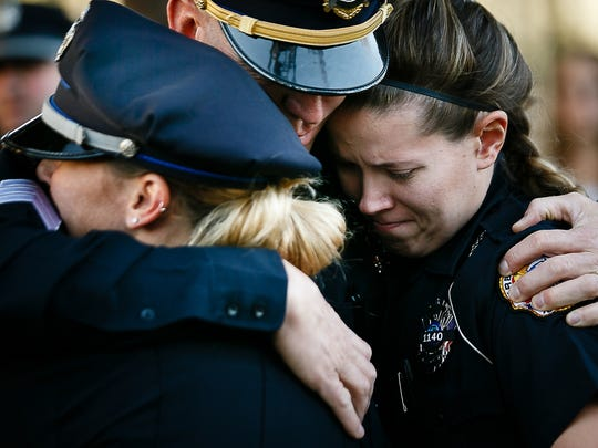 Sgt. Mark Jorgensen embraces Officer Justice Weaver, left, and Officer Elisabeth Carr, right,  before a candle light vigil in honor of Officer Justin Martin and Sgt. Anthony Beminio on Friday, Nov. 4, 2016 in Urbandale. The two police officers were killed two miles apart while on duty early Wednesday morning.
