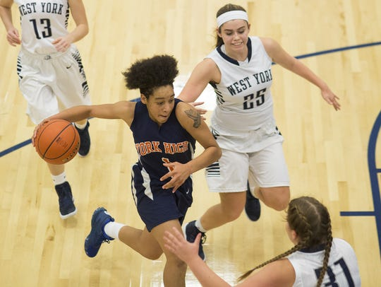 William Penn's Madey-Zania Redman, center, drives to
