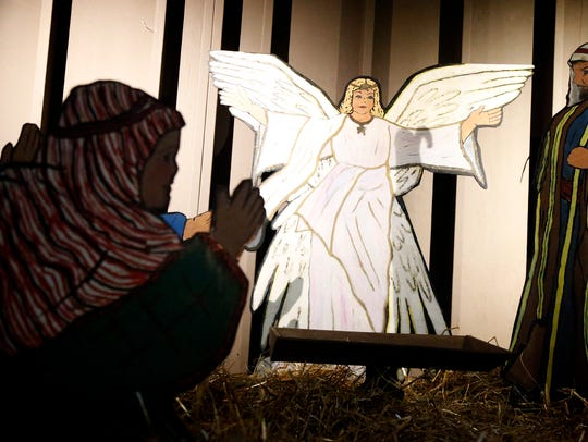 An angel towers over an empty manger where baby Jesus