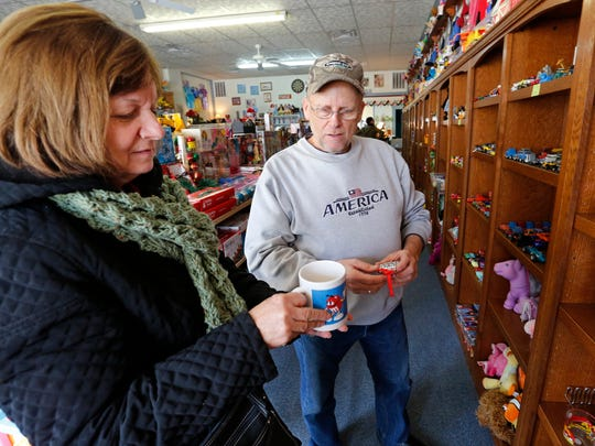 Lee Brunton and his wife Jolinda look at M&M'S candy-themed collectibles Tuesday, December 20, 2016, at the Romney Toy Shop. Since 2001, owner Terri Barnes has given new life to a variety of older, gently used toys and collectibles.