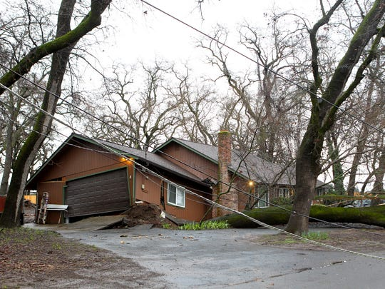 A house is severely damaged after a tree was uprooted Tuesday off Fagan Drive in Redding.