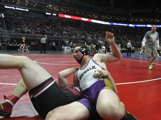 Norwalk junior 220-pounder Drake Leek (in white,purple and gold) wrestles Waterloo Wet senior Sam Gerst in a Class 3A quarterfinal match Feb. 17 at the state wrestling tournament at Wells Fargo Arena in Des Moines. Gerst won an ultimate tie-breaker to win 8-7.