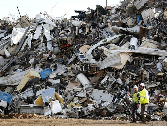 John Eide and Mark Lasky walk past a pile of scrap