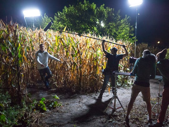 "Actor Mitch Westphal emerges from a corn maze while shooting scenes for the feature film ""Spiral,"" as Rue Dwyer holds a boom microphone for sound, Ben Handler shoots video, and Joe Clarke directs at Colony Pumpkin Patch in North Liberty in the early morning hours of September 11, 2016. The film was written and directed by Joe Clarke and shot on location in Iowa City and North Liberty."