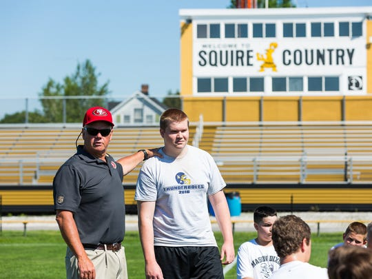 """The press box at J.T. Flaherty Field has Francis Rineman's trademark, """"Welcome to Squire Country"""" written across it. Here, Delone grad and former San Francisco 49ers offensive line coach J.T. Flaherty instructs high school players at the field last summer."""