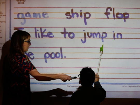 Clarence Farrington School 61 kindergarten teacher Alyssa Collin holds her microphone at a level student David Alex Turdos can reach as he reads a sentence allowed to the class on Thursday, May 4, 2017.