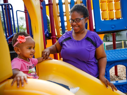 Adrienne Brown helps daughter, Olivia, 1, down the slide on the playground at Wheeler Mission Center for Women & Children on Wednesday, July 12, 2017.