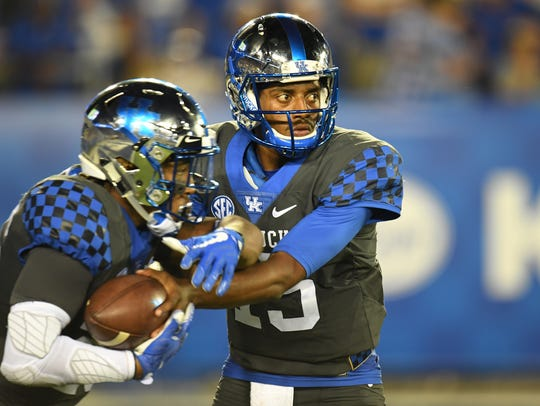 UK QB Stephen Johnson hands off the ball during the