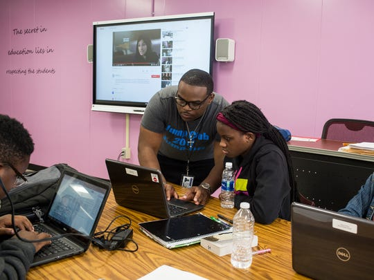 September 28, 2017 - Joseph Perry, a college success coach with Peer Power, helps Jayoa Webb with her classwork at East High School.