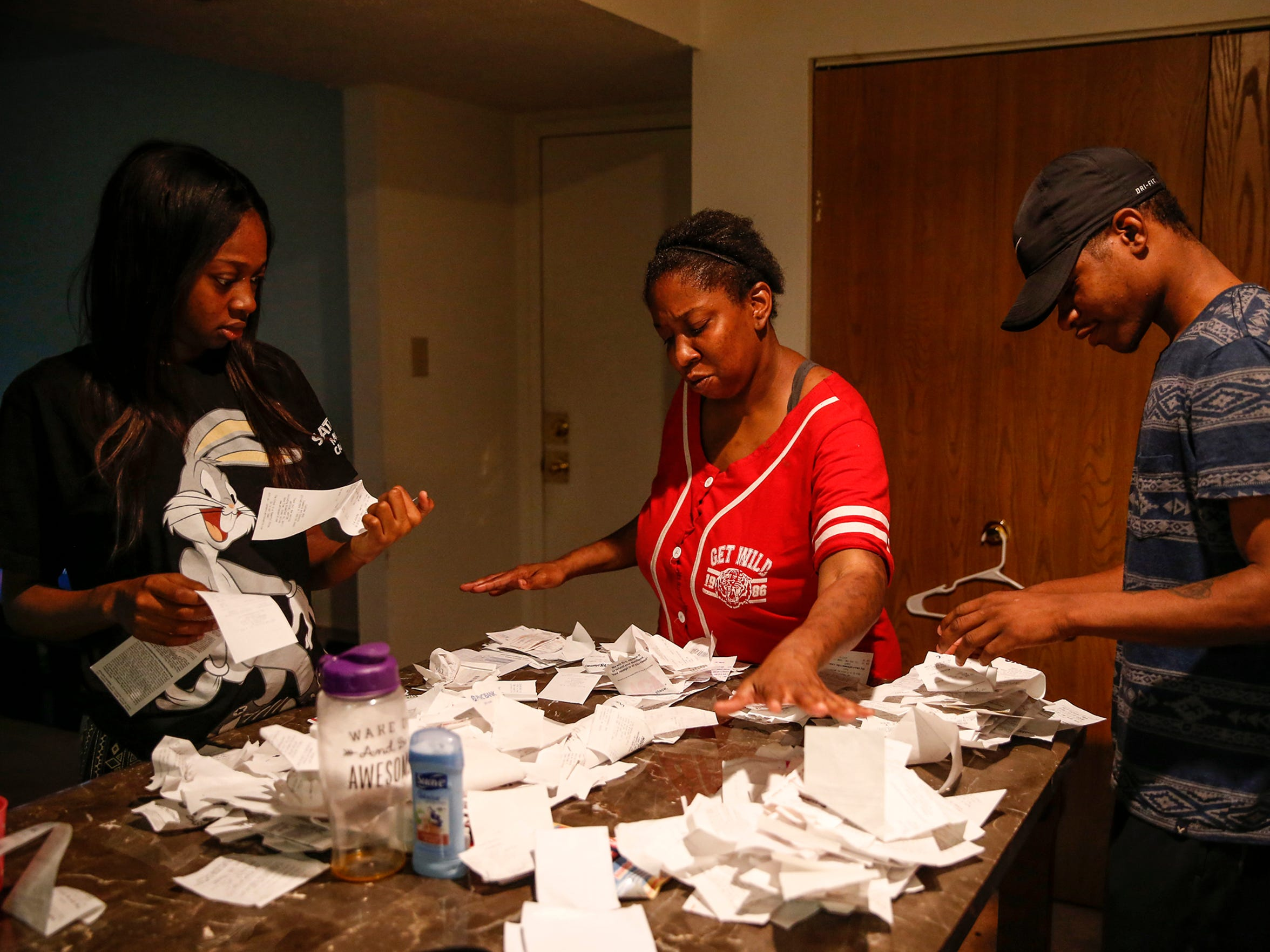 "De'Janae, left, her mother and boyfriend, Richard Ceaser, search for a diaper receipt on Saturday, May 20, 2017. Simpson wants to return a box for a different size. Ceaser, though not the father of De'Janae's baby, has been helping her throughout her pregnancy. From doctors appointments to providing money help, Ceaser says he'll treat the baby like his own. ""I'm excited to take her to your volleyball games,"" he said. ""We'll sit in there and cheer for you."" De'Janae isn't sure if she'll be able to return to the sport she loves after giving birth."