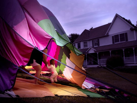 Savannah and her mom Cassandra explore a hot air balloon that landed in their neighbor's front yard on Friday, July 28. 2017.