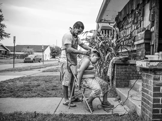 Albert Morales cuts the hair of Brian Sanchez, 13, in between rain showers in Near West on Thursday, July 6, 2017.