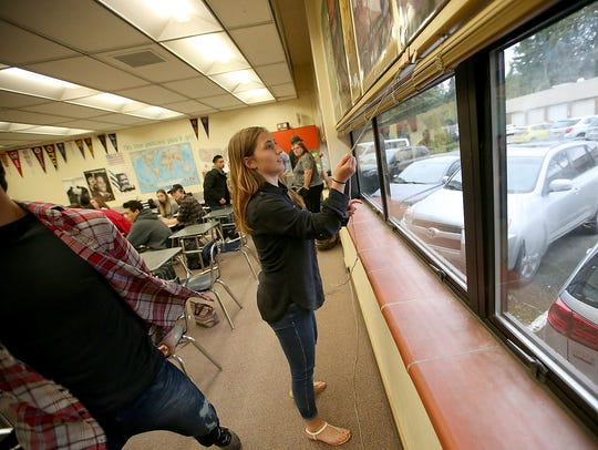 Student Calli Frisinger, 18, lowers the blinds in the classroom during a school safety drill at Central Kitsap High School.