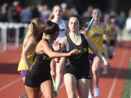 Carlisle's Ashliah Hyde reaches back to take the baton from Madi Watts. The Simpson College High School Classic was held March 26 in Indianola.