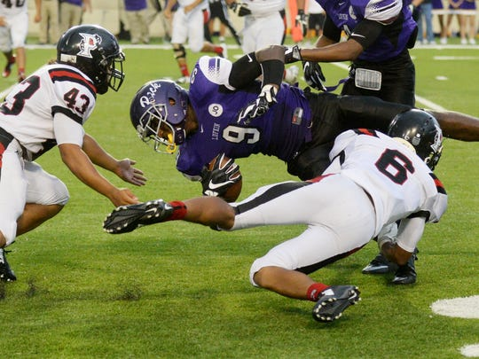 Parkway'sDavid Morales, left, and Jaylon Hall takes down Lufkin's Breylon Garcia during the Battle on the Border Saturday at Independence Stadium.