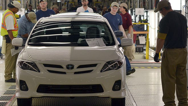 Workers do a final inspection of Toyota Carollas before they are drive off the assembly line at the Toyota plant near Tupelo, Miss.