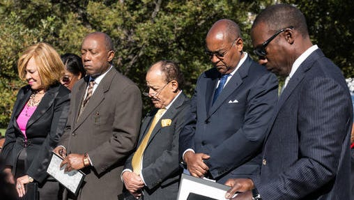 Members of the Texas Legislative Black Caucus, and the Texas African American History Memorial Foundation, bow their heads in prayer before the unveiling of the African American History Memorial outside the Texas State Capitol in Austin, Texas, on Saturday, Nov. 19, 2016.