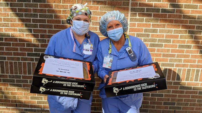 Hospital employees pose with donut boxes from SpartanNash, which reached out to frontline workers to show appreciation early in the pandemic. Now, the company is raising money for local food pantries through its grocery stores.