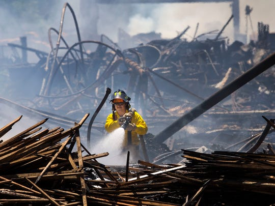 A firefighter from McKenzie Fire and Rescue works to douse hotspots on the edge of the Whitsell Manufacturing mill site Monday May 28, 2018 the day after a massive fire leveled much of the site in Saginaw, Ore. (Chris Pietsch/The Register-Guard via AP)