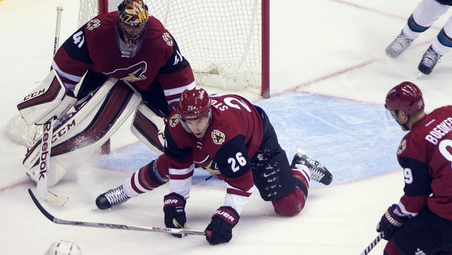 Coyotes goalie Mike Smith and Michael Stone (26) block a shot from the Sharks' Joel Ward during their preseason game at Gila River Arena on Oct. 2, 2015.