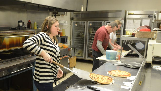 Jessica Johnson removes pizzas from the oven as Joe Szabo and Bethany Paul prepare food orders in the kitchen at Bell Mell's.