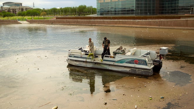 Workers with Aquatic Consulting & Testing, Inc., remove vegetation from a mixture of sludge, green algae and garbage pooling near the western end of Tempe Town Lake after the recent storms. City officials say it is going to take a continual cleanup process to clear the water.