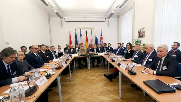 The European Union's political director Helga Schmid and Iran's deputy Foreign Minister Abbas Araghchi, center from left, wait for a bilateral meeting as part of the closed-door nuclear talks with Iran in Vienna, Austria on Dec. 6, 2019.