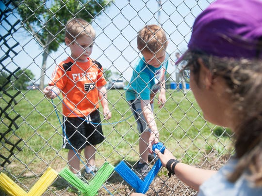 (From left) 4-year-old Seth Bucci and his brother 7-year old Ethan Bucci, both of Glassboro, work with Glassboro native Meridith Daniel to create a fiber art piece in the New East Street Park in Glassboro on Saturday.
