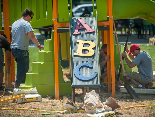Volunteers work to build a playground in the East New