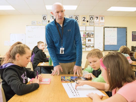 Jason Rohr, one of six members of the Kewaunee School District's special education team, works with students on a word problem. The team is one of seven winners of 2018 Golden Apple teaching awards.