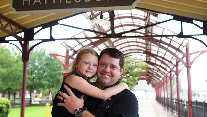 Chris Price and his oldest daughter Josie take a photo together at the Hattiesburg Train Depot. Price helped round up and organize volunteers after tornadoes hit Hattiesburg in 2013 and 2017.