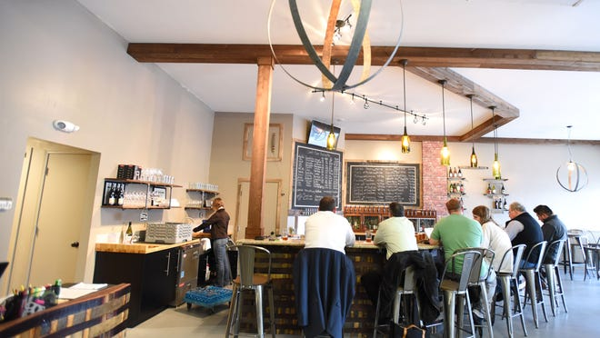 Customers sit at the bar at Barrel & Keg bottle shop on Tuesday. The shop features a variety of fine wines and craft beers. A grand opening will be held on March 27 and 28.
