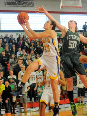 Birmingham Marian's Brittany Gray drives past Waterford Kettering's Haley Tewes. Marian won 51-42 in the Class A quarterfinals Tuesday.