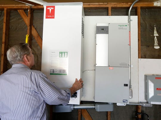In this April 20, 2015 photo, David Cunnigham shows a prototype Tesla battery system that powers his Foster City, Calif. home. Cunnigham installed the battery late last year to pair with his solar panels as part of a pilot program run by the California Public Utilities Commission to test home battery performance. Tesla is expected to unveil a stationary battery for homeowners and businesses on Thursday, April 30, 2015. (AP Photo/Jeff Chiu)