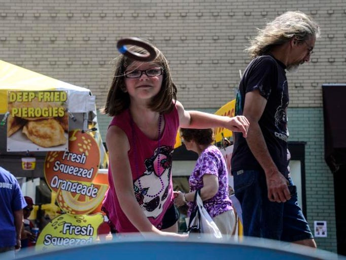 Olivia Schiraldi, 8, of Binghamton, tosses a ring while playing a game during the 52nd annual July Fest in downtown Binghamton.
