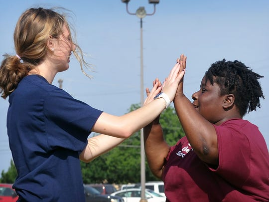 Special Olympian Makayla Meeks, right, is congratulated by volunteer Addison Stahler after scoring well in the football toss event at the Special Olympics Unified Sports Day at Rider High School.