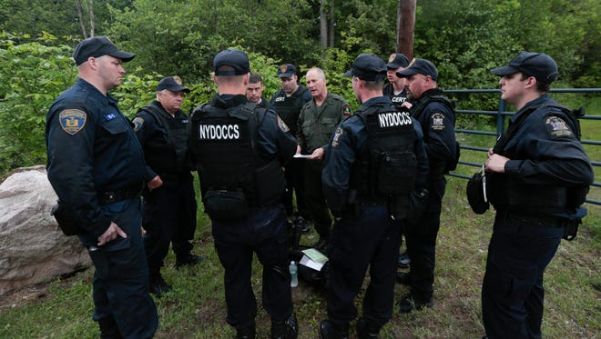State forest ranger Dan Fox reviews a map with members of the New York State Department of Corrections and Community Supervision emergency response team before entering a wooded area in search of two prisoners who escaped from the Clinton Correctional Facility on June 8, 2015, in Dannemora, N.Y.