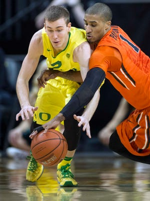 Feb 20, 2016; Eugene, OR, USA; University of Oregon Ducks guard Casey Benson (2) dives for a loose ball against Oregon State University Beavers guard Gary Payton II (1) during the second half at Matthew Knight Arena. The Ducks beat the Beavers 91-81. Mandatory Credit: Troy Wayrynen-USA TODAY Sports