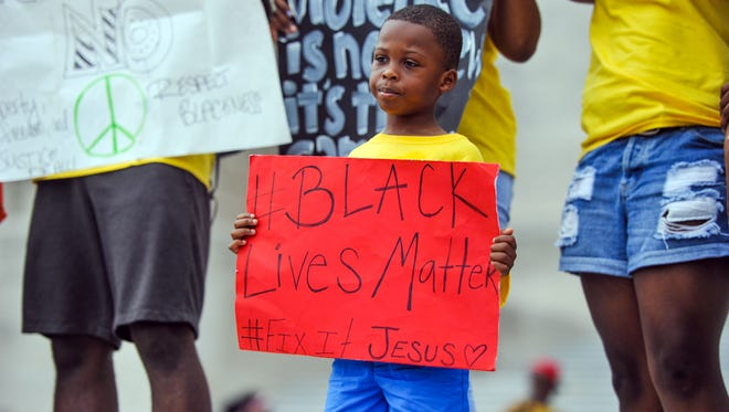 """A child holds a """"Black Lives Matter"""" poster during a July 10, 2016, peace march from   Wesley United Methodist Church to the Louisiana State Capitol in Baton Rouge. Alton Sterling, unarmed, was shot by Baton Rouge police five days earlier."""