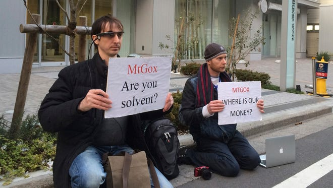 Bitcoin trader Kolin Burges, right, of London and American Aaron (only his first name was given) hold protest signs as they conduct a sit-in in front of the office tower housing Mt. Gox in Tokyo.