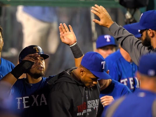 Texas Rangers' Rougned Odor, left, is congratulated by teammates after scoring on a ground-front out by Jake Smolinski during the seventh inning of a baseball game against the Los Angeles Angels, Saturday, Sept. 20, 2014, in Anaheim, Calif. (AP Photo/Mark J. Terrill)
