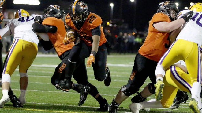 Massillon's Reece Turpin, left and Rager Els, right, open up the hole for Zion Phifer to run through during the Tigers' Division II state semifinal win over Avon last year.