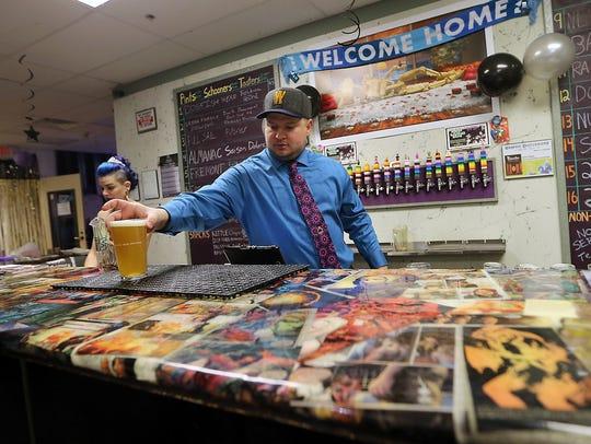 Thor Bjork serves up a pint to a customer at Ashley's Pub.