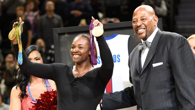 Olympic Gold medalist Claressa Shields is honored by the Pistons during the second quarter. Former Pistons player Earl Cureton is to the right.