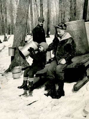 Michael takes a look into one of the sap buckets while his older brother John and their father Clarence look on.